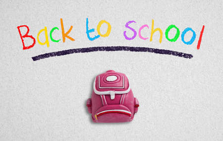 """message """"back to school"""" and a backpack piece on paper background Foto de archivo"""