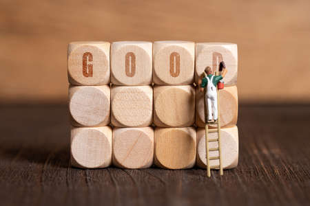 little painter figure and the word GOOD on wooden background 写真素材