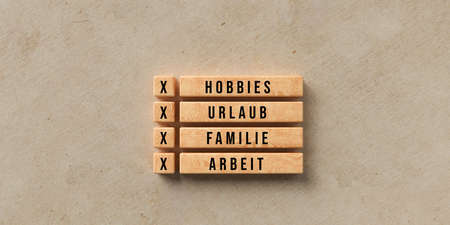 wooden blocks with the German words  for HOBBIES, VACATION, FAMILY and WORK on paper background - 3D rendered illustration 写真素材
