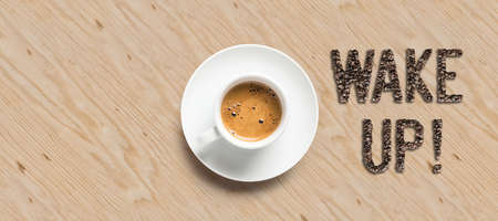 cup of coffee and text WAKE UP! on wooden background