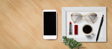 feminine flat lay with smartphone, lipstick, glasses, a coffee and a pen on wooden background 写真素材