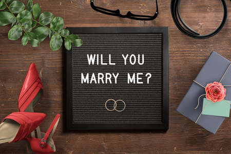 letter board with proposal text will you marry me? on wooden background