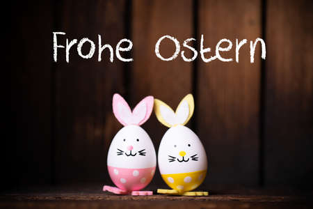Easter Eggs with bunny ears and message Happy Easter in German on wooden background