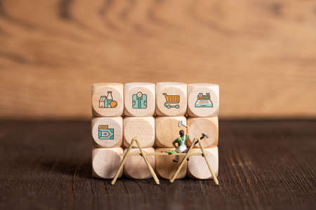 little painter figure and cubes with sales icons on wooden background
