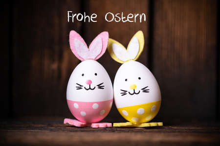 "Easter Eggs with bunny ears and message ""Happy Easter"" in German on wooden background"