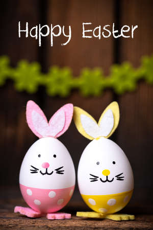 "Easter Eggs with bunny ears and message ""Happy Easter"" on wooden background"