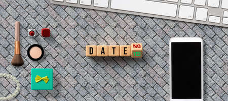 wooden blocks with the word DATE and the option between NO and YES on stone background with smartphone, keyboard and cosmetica