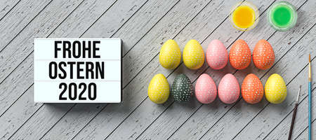 easter eggs and lightbox with message HAPPY EASTER 2020 in German surrounded by water color boxes on wooden background