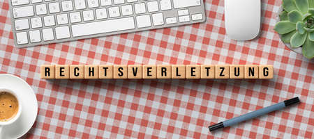 cubes with message RIGHT VIOLATION in German with computer equipment on tablecloth background Foto de archivo
