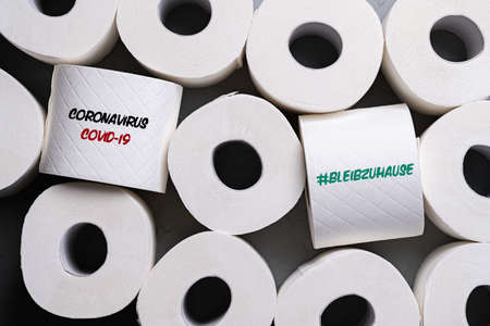 toilet paper rolls with message COVID-19 and German message for #STAYATHOME