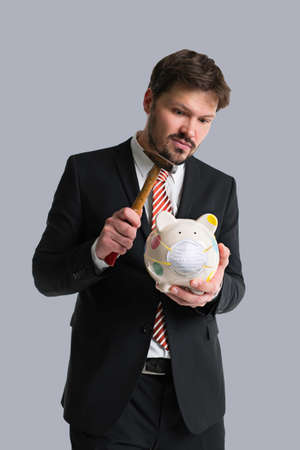 businessman breaking a piggy bank with a face mask on it in front of grey background