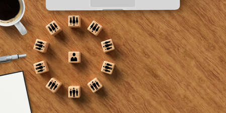 cubes with people symbols forming a circle around a single person and a computer on wooden background