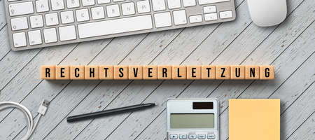 cubes with message RIGHT VIOLATION in German with computer equipment on wooden background