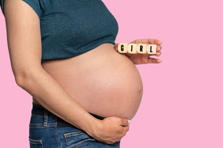 pregnant woman holding cubes with message GIRL