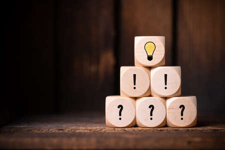 cubes with question marks, exclamation marks and a lightbulb symbol in front of wooden background Stock Photo