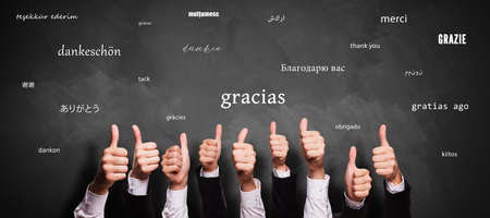 many thumbs up and blackboard with message THANK YOU in different languages