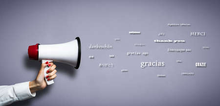 hand with megaphone and the word THANK YOU in many languages on blue background