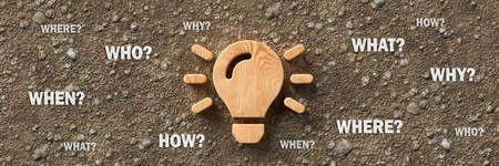 wooden lightbulb on dirt gravel background with the words WHEN, WHAT, WHERE, WHO, WHY and HOW - 3d illustration Banque d'images