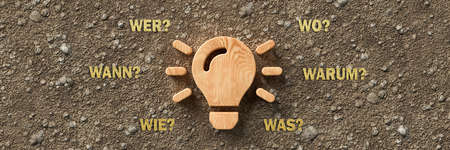 wooden lightbulb on dirt gravel background with the German words for WHEN, WHAT, WHERE, WHO, WHY and HOW - 3d illustration Banque d'images