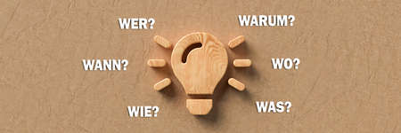 wooden lightbulb with the German words for WHEN, WHAT, WHERE, WHO, WHY and HOW on paper background - 3d illustration Banque d'images