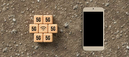 cubes with 5G and WLAN symbol with smartphone on gravel background