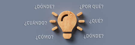 wooden lightbulb with the Spanish words for WHEN, WHAT, WHERE, WHO, WHY and HOW on colorful background - 3d illustration