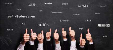 many thumbs up and blackboard with message GOODBYE in different languages Zdjęcie Seryjne