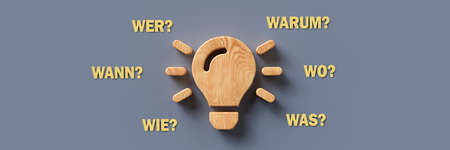wooden lightbulb with the German words for WHEN, WHAT, WHERE, WHO, WHY and HOW on colorful background - 3d illustration