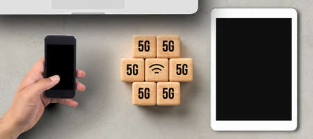 cubes with 5G and WLAN symbol besides tablet, smartphone, and laptop on concrete background