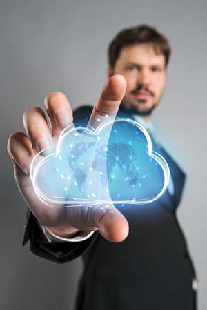 businessman interacting with a virtual cloud in front of grey background