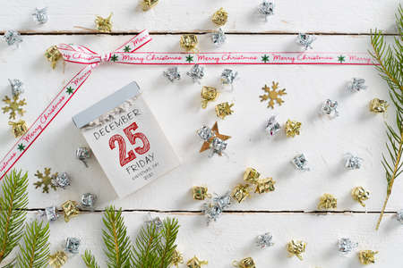 tear-off calendar with Christmas Day 2020 on top surrounded by christmas decoration on wooden background