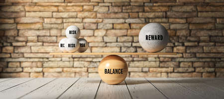 wooden scale balancing one big ball and four small ones with message RISK, REWARD and BALANCE in front of a brick wall - 3d illustration Standard-Bild