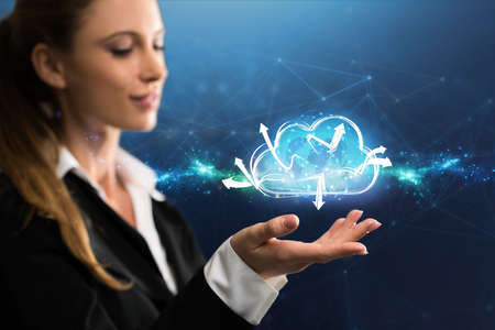 businesswoman interacting with a virtual cloud in front of blue background