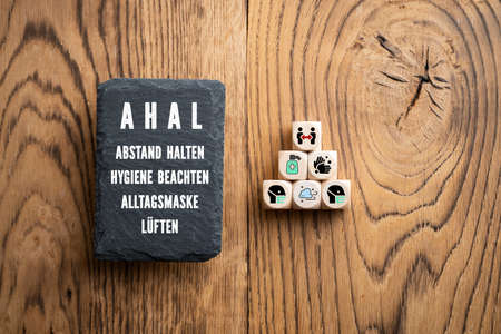 German acronym AHAL and German explanation for the four rules in a pandemic DISTANCE, HYGIENE, FACE MASKS and VENTILATION on writing slate in front of wooden background Stock Photo