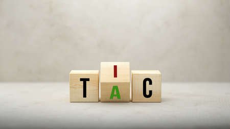 Tic - Tac concept with revolving letters A and I on wooden blocks over a grey background viewed low angle with copyspace - 3d illustration