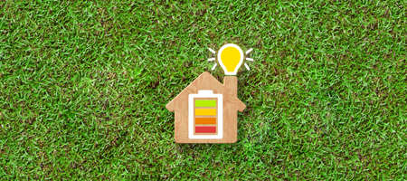 Energy efficiency and rating chart in a small model house with glowing lightbulb in the chimney over green grass in an ecological and environmental concept - 3d illustration