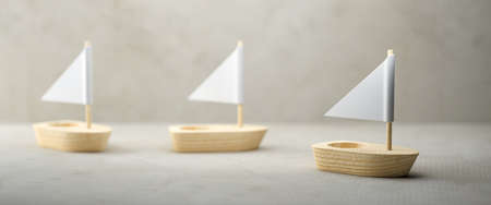 Conceptual image of three simple little wooden sailboats with sails over a grey background conceptual of adventure, exploration, voyage or a spiritual journey - 3d illustration