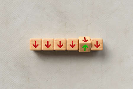 Line of down pointing red arrows on wooden cubes with one green arrow pointing up in a concept of individuality, success or leadership over grey with copyspace - 3d illustration 版權商用圖片
