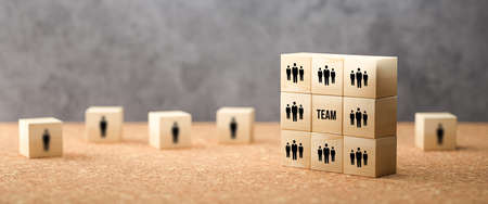 cube with message TEAM surrounded by cubes with person symbols on cork surface in front of concrete background - 3d illustration