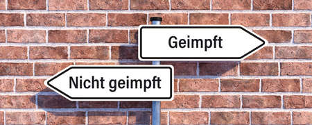 street sign with German message for VACCINATED and a crossed NOT VACCINATED in front of a brick wall - 3d illustration