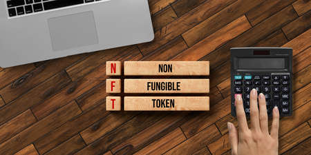wooden blocks with message NFT - NON FUNGIBLE TOKEN and a hand over a calculator on wooden background 版權商用圖片