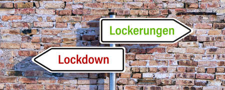 two street signs pointing in different directions showing the German message for LOCKDOWN and EASING in front of a brick wall - 3d illustration