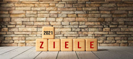 wooden cubes with the German message for GOALS 2021 on wooden surface in front of a brick wall - 3d illustration 版權商用圖片