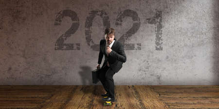 businessman on a skateboard in front of a concrete wall with message 2021 版權商用圖片