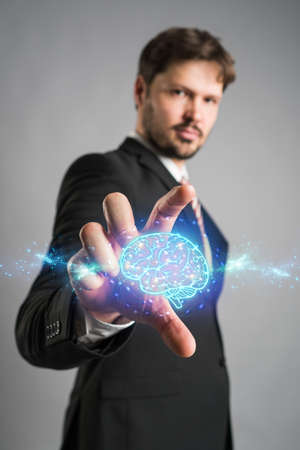 Businessman reaching forwards to grasp an AI icon of a shining blue brain emitting energy and power on a virtual interface or computer screen