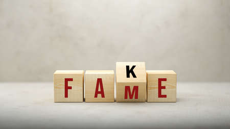 Fame or Fake concept with revolving letters on wooden cubes viewed low angle over a grey background with copyspace above - 3d illustration
