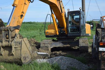 earthmover: Bucket of the excavator on installation of the basis of electrocolumns. Stock Photo