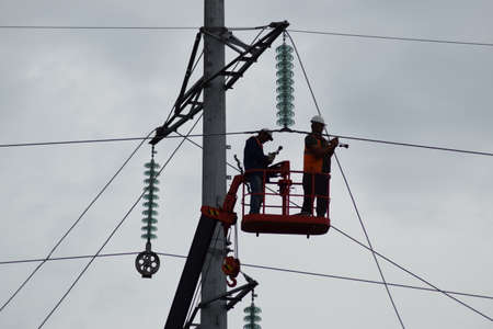 powerfully: Electrician lineman repairman worker at climbing work on electric post power pole