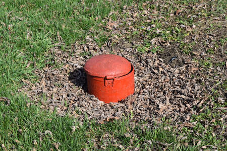 sewerage: Hatch steel, red color. in park there is a sewerage Stock Photo