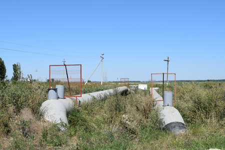 cement chimney: The gas pipeline through the small river. Equipment of oil and gas crafts. Stock Photo